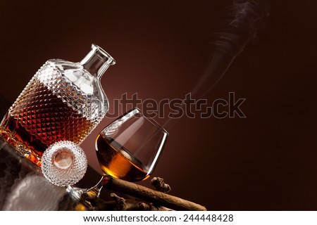 A fine alcohol and a smoking cigar - stock photo