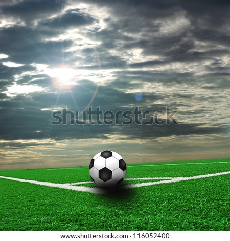 A fine green meadow with a soccer ball on it. All on sky sunset - stock photo