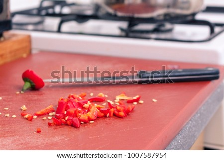 A finely chopped red chilli pepper on a chopping board in a domestic kitchen