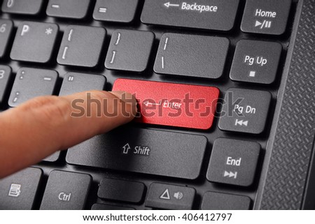 A finger pressing the Enter button on a laptop keyboard, close up shot