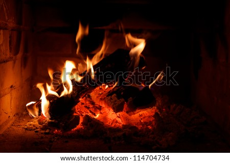 A fire burning in an open fire place - stock photo