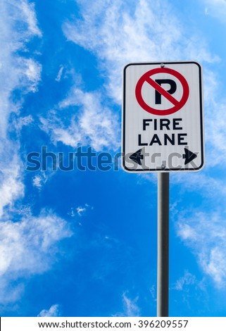 A Fire Lane No Parking sign against a blue cloudy sky with copy space. Vertical orientation.