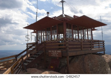 A fire lookout watchtower perches on the edge of a cliff on top of the Devil's Head rock formation in central Colorado - horizontal orientation in closeup. - stock photo
