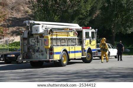 A firefighter and police officer controlling traffic in a neighborhood - stock photo
