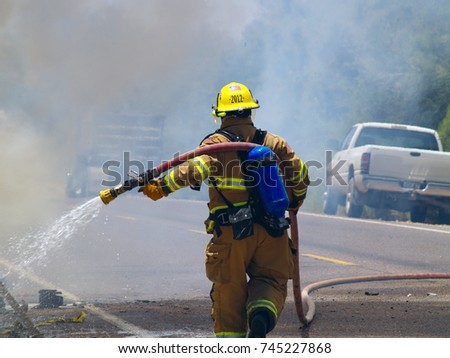 A firefighter extinguishing a vehicle fire along an Arizona road. Firefighter's face is not visible, no model release is necessary.