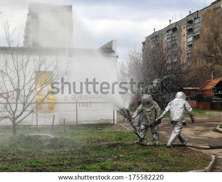 A firefighter wetting down hotspots of a structure fire - stock photo