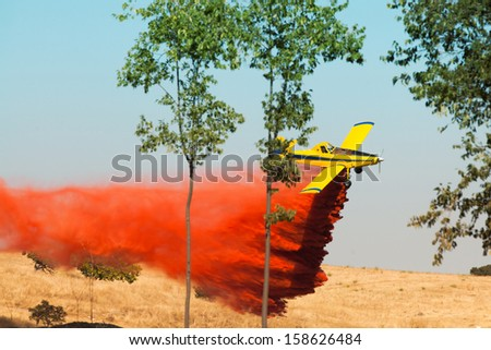 A firefighting plane discharging retardant in a fire - stock photo