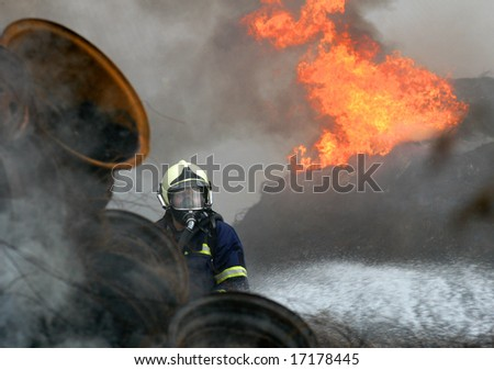A fireman estinguishing fire of tyres