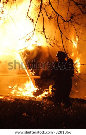 A fireman fighting a raging house fire in the middle of the night - stock photo