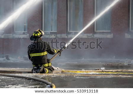 A fireman kneels in the middle of wet, icy road. He is using a hose to spray water. Fire hoses are on the ground. The building is in the background with smoke and spray in front of it.