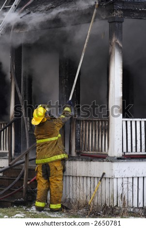 A Fireman putting out the fire on the porch of a Detroit abandoned house
