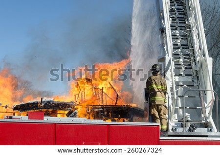 A fireman standing at the controls of an 105 foot reach aerial ladder/truck directs a stream of water on a blazing building. - stock photo