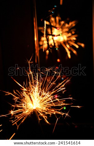 A firework sparkler that is safe for children to hold in their hand. Taken on new years eve. It�´s giving beautiful stars and sparkles. - stock photo