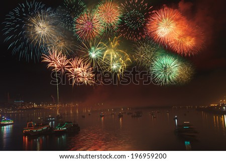 A fireworks display over a bay filled with boats. - stock photo
