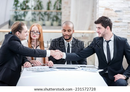 A firm handshake. Four successful businessman sitting at the table at a business meeting in the office while two businessmen shaking hands