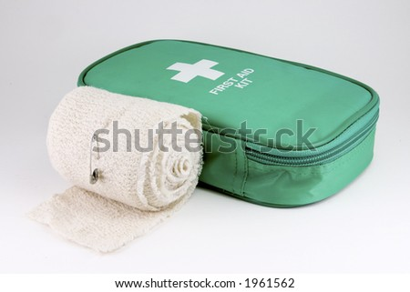 A first aid kit on white with bandage roll. - stock photo