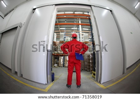 A fish eye view of a worker standing in the doorway of a modern industrial facility. - stock photo