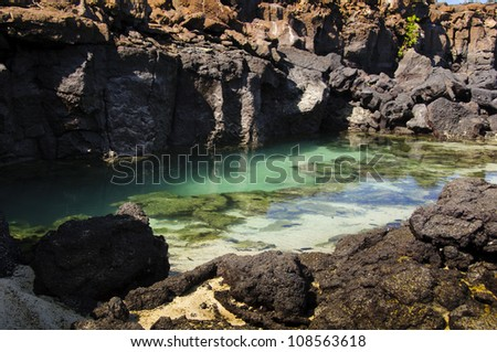 A fish-filled, salt-water pool in a rocky enclave in the Galapagos Islands - stock photo