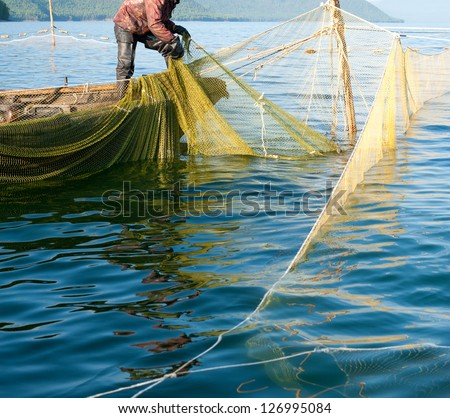 a fisher on a boat hauls a seine - stock photo