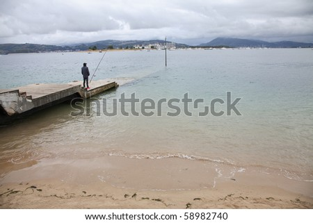 a fisherman and the fishing rod on the dock at the beach