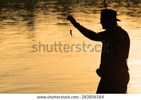 A fisherman caught a small fish  - stock photo