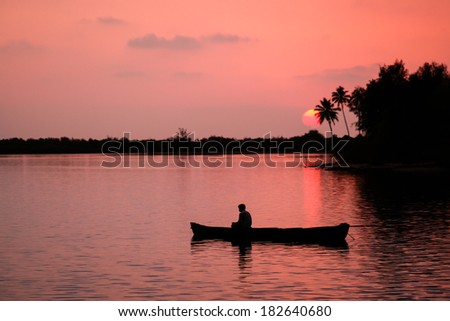 A fisherman drifting downriver in his boat during a red tropical sunset.