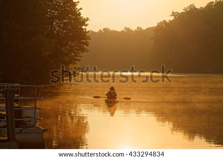 A fisherman on a kayak at sunrise. - stock photo