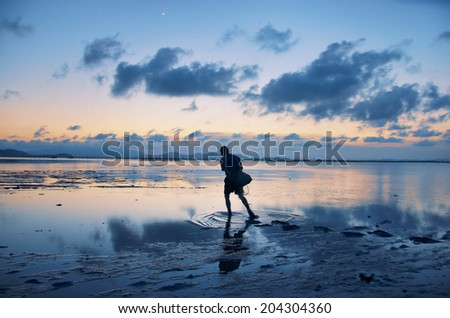 A fisherman on the beach at dusk