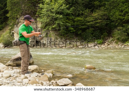A fisherman on the river bank. Fishing as an active lifestyle. Fishing on the mountain river. Fisherman standing on a rock fishing.