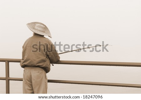 A fisherman relaxes during a cold, foggy morning.