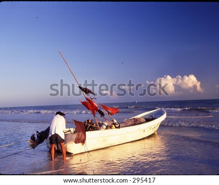 a fisherman securing his boat on the beach in isla holbox, mexico.