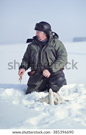 A fisherman sits on the ice with a fishing rod, and next is the fish. Winter fishing. - stock photo