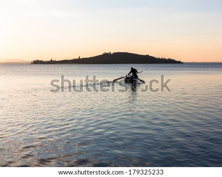 A fisherman tends his nets on Lago Trasimeno, Perugia, Italy at dusk.  The lake is a shallow muddy lake abundant with fish