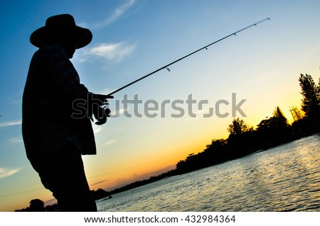 A fisherman, who is fishing on the lake in evening. sunset background. - stock photo