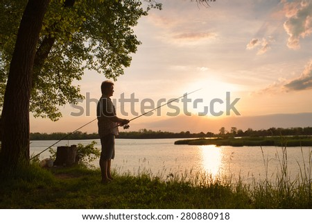 A fisherman with a fishing rod on the river bank  - stock photo