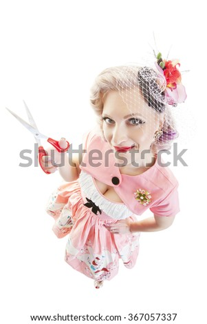A fisheye view, pretty in pink pinup girl with scissors.  Shot on white background.