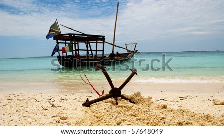 A fishing boat anchored by the beach in Zanzibar - stock photo