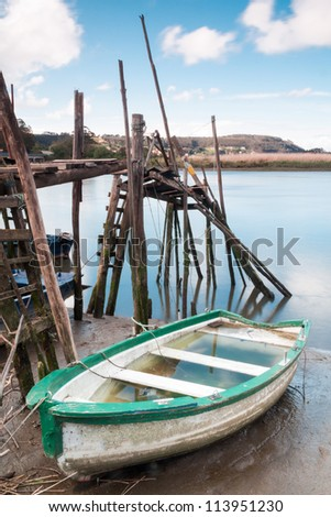 A fishing boat full of water near a pier - stock photo