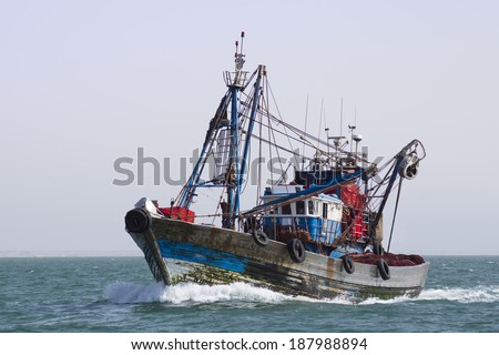 A fishing boat is at sea fishing. Sunny. - stock photo