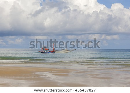 a fishing boat on a sea with beach and cloud