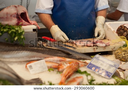 a fishmonger preparing and cutting fresh fish on market - stock photo