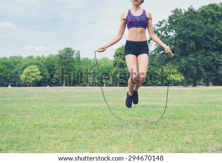 A fit and athletic young woman is skipping with a jump rope in the park on a summer day - stock photo