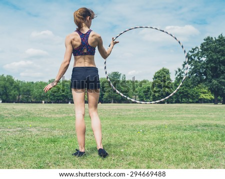 A fit and athletic young woman is twirling a hula hoop in the park on a sunny summer day