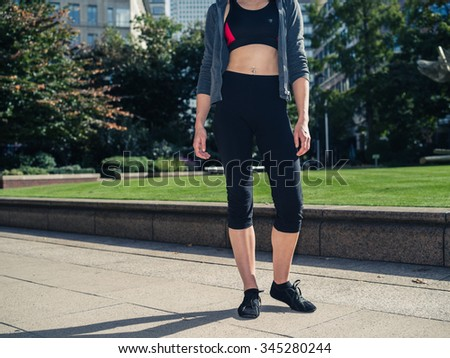A fit and athletic young woman with toned abs is standing in a city park on a sunny day - stock photo