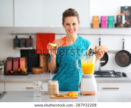 A fit brunette smiles happily as she is adding apple to her freshly-made smoothie. Nothing like a boost of vitamins to round out your workout...