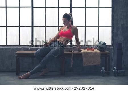 A fit, buff, muscular woman is sitting, relaxed, on a wooden bench in her local loft gym. Looking down at her phone, she is selecting the music she would like to listen to for her workout. - stock photo