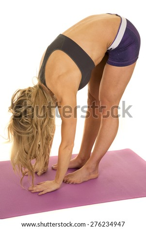 a fit woman bending over stretching her body.