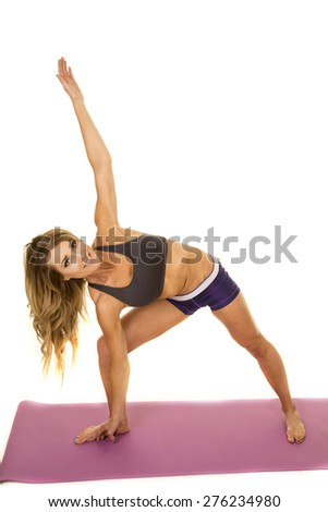 A fit woman doing a body stretch with a smile.