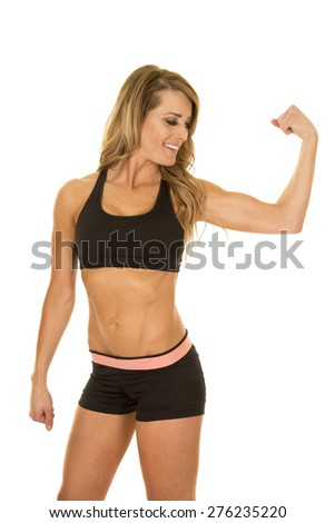 a fit woman in her sports bra and shorts, flexing her muscles with a smile on her face. - stock photo