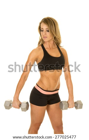a fit woman in her sports bra and spanks looking over her shoulder while she lifts, weights.